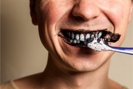 Man brushing teeth with charcoal teeth whitening products